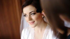 Η χαριτωμένη παράνυμφος μπλε να ισχύσει φορεμάτων αποζημιώνει μια νέα όμορφη νύφη που φορά την άσπρη εσθήτα υπολοίπου μεταξιού κα φιλμ μικρού μήκους