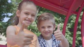 Η χαριτωμένη παρουσίαση αγοριών και κοριτσιών φυλλομετρεί επάνω να καθίσει στην ταλάντευση κοντά επάνω στο πάρκο, εξετάζοντας τη  απόθεμα βίντεο