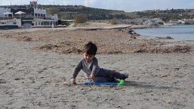 Η χαριτωμένη συνεδρίαση μικρών παιδιών στην άμμο και το παιχνίδι με το πλαστικό γκολφ κολλούν και άμμος στην παραλία φιλμ μικρού μήκους