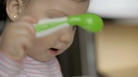Η χαριτωμένη συνεδρίαση μωρών gil στη σίτιση προεδρεύει και την κατανάλωση των υγιών τροφίμων στην κουζίνα απόθεμα βίντεο