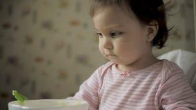 Η χαριτωμένη συνεδρίαση μωρών gil στη σίτιση προεδρεύει και την κατανάλωση των υγιών τροφίμων στην κουζίνα φιλμ μικρού μήκους