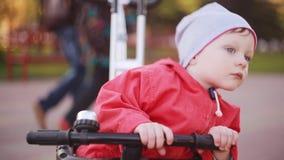 Η χαριτωμένη συνεδρίαση μικρών παιδιών στο ποδήλατο, κρατά το χέρι στη ρόδα Παιδί στο κόκκινο σακάκι που προετοιμάζεται στην οδήγ απόθεμα βίντεο