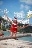 Η χαριτωμένη χαρούμενη γυναίκα πηδά στο κόκκινα φόρεμα, τα γυαλιά ηλίου και το καπέλο santa στην εξωτική τροπική παραλία Έννοια δ Στοκ Εικόνες