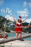 Η χαριτωμένη χαρούμενη γυναίκα πηδά στο κόκκινο καπέλο φορεμάτων και santa στην εξωτική τροπική παραλία Έννοια διακοπών για τις ν Στοκ Εικόνες