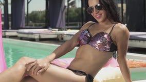 Η χαριτωμένη smilling γυναίκα στο ασημένιο κοστούμι swimmimg κάνει ηλιοθεραπεία τη συνεδρίαση στην πλευρά πισινών, πόδια στο νερό απόθεμα βίντεο