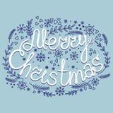 Η Χαρούμενα Χριστούγεννα επιγραφής με τα στοιχεία Χριστουγέννων σε ένα blu Στοκ εικόνες με δικαίωμα ελεύθερης χρήσης