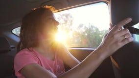 Η χαρούμενη γυναίκα απολαμβάνει με το αυτοκίνητο στο καλοκαίρι Ακτίνες ηλιοβασιλέματος κίνηση αργή φιλμ μικρού μήκους