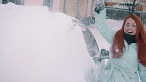 Η χαρούμενη γυναίκα καθαρίζει το χιόνι από το αυτοκίνητό της απόθεμα βίντεο
