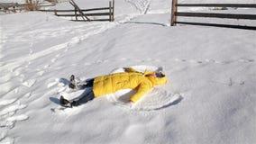 Η χαρούμενη γυναίκα παίζει στο χειμερινό αγώνα Το κορίτσι στο κίτρινο σακάκι Bringh βρίσκεται στο έδαφος και κάνει τον άγγελο χιο απόθεμα βίντεο