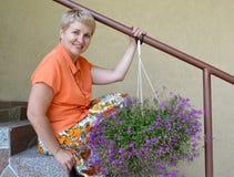 Η χαρούμενη γυναίκα των μέσων ετών κάθεται σε μια σκάλα με τα διακοσμητικά λουλούδια ένα lobelia Στοκ Εικόνα