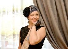 Η χαρούμενη γυναίκα των μέσων ετών σε ένα καπέλο με ένα πέπλο και ένα μαντίλι σε ένα χέρι ενάντια σε ένα παράθυρο Στοκ εικόνες με δικαίωμα ελεύθερης χρήσης