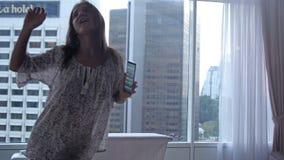Η χαρούμενη γυναίκα brunette χορεύει κοντά στα πανοραμικά παράθυρα απολαμβάνοντας τη μουσική με το κινητό τηλέφωνο στο διαμέρισμα απόθεμα βίντεο
