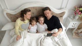 Η χαρούμενη οικογένεια παίρνει Selfie χρησιμοποιώντας Smartphone Το χαριτωμένα αγόρι και το κορίτσι φιλούν τους γονείς τους στο κ απόθεμα βίντεο
