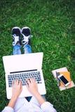 Η χαλαρώνοντας ψύχρα χώρου εργασίας λειτουργεί έξω για το γραφείο και το smartphone lap-top σχεδίου στοκ φωτογραφία