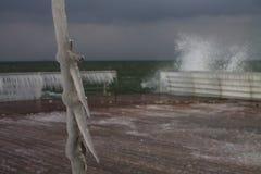 Η χειμερινή θύελλα καλύπτει τα καλώδια στην αποβάθρα με τα παγάκια στοκ εικόνα