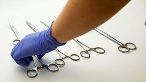 Η χειρουργική νοσοκόμα επιλέγει τα ιατρικά εργαλεία επάνω στη χειρουργική επέμβαση Στοκ Εικόνες