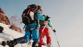 Η χιονισμένη βουνοπλαγιά, μέσω των βαθιών κλίσεων γλιστρά μια ομάδα ορειβατών απόθεμα βίντεο