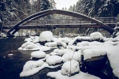 Η χιονώδης ξύλινη γέφυρα πέρα από το χειμερινό ποταμό Στοκ Εικόνες