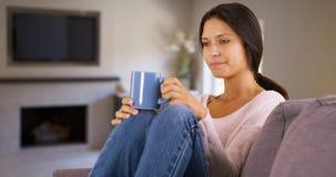 Η χιλιετής λευκή γυναίκα κάθεται ευτυχώς στον καφέ κατανάλωσης καναπέδων της στοκ φωτογραφία με δικαίωμα ελεύθερης χρήσης