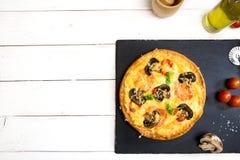 Η χορτοφάγος πίτσα με τα μανιτάρια εξυπηρέτησε στον άσπρο ξύλινο πίνακα και τη μαύρη επιφάνεια πετρών έτοιμος να φάει Στοκ φωτογραφία με δικαίωμα ελεύθερης χρήσης