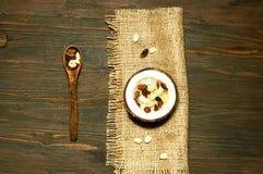 Η χορτοφάγος σαλάτα με τα ξέσματα καρύδων και τα καρύδια στην καρύδα κυλούν στο ξύλινο υπόβαθρο στοκ φωτογραφία
