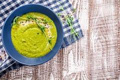 Η χορτοφάγος σούπα πράσινων μπιζελιών με στο μπλε ύφασμα και το ξύλινο άσπρο υπόβαθρο στοκ φωτογραφίες