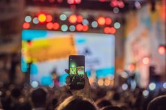 Η χρήση προώθησε την κινητή καταγραφή, συναυλίες διασκέδασης και ο όμορφος φωτισμός, ειλικρινής εικόνα του πλήθους στη συναυλία β στοκ εικόνα με δικαίωμα ελεύθερης χρήσης