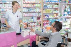 Η χρήσιμη εξυπηρέτηση φαρμακοποιών θέτει εκτός λειτουργίας το άτομο στο φαρμακείο στοκ φωτογραφίες