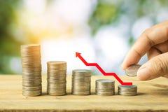 Η χρηματοδότηση και σώζει την έννοια χρημάτων, νομίσματα σωρών χεριών με το κόκκινο βέλος Στοκ εικόνα με δικαίωμα ελεύθερης χρήσης