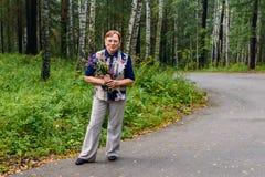 Η 60χρονη γυναίκα στο παντελόνι στέκεται στο δρόμο στο πάρκο με μια ανθοδέσμη των άγριων λουλουδιών στην πλήρη αύξηση και εξετάζε στοκ φωτογραφία