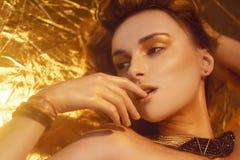 Η χρυσή μόδα Makeup, το πρόσωπο ομορφιάς τέχνης και τα χείλια αποτελούν στο χρυσό μπροκάρ Χρυσό πορτρέτο προσώπου γυναικών δερμάτ στοκ φωτογραφία με δικαίωμα ελεύθερης χρήσης