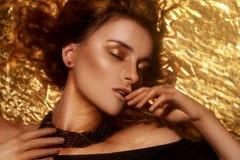 Η χρυσή μόδα Makeup, το πρόσωπο ομορφιάς τέχνης και τα χείλια αποτελούν στο χρυσό μπροκάρ Χρυσό πορτρέτο προσώπου γυναικών δερμάτ στοκ εικόνες με δικαίωμα ελεύθερης χρήσης