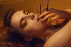 Η χρυσή μόδα Makeup, το πρόσωπο ομορφιάς τέχνης και τα χείλια αποτελούν στο χρυσό μπροκάρ Χρυσό πορτρέτο προσώπου γυναικών δερμάτ στοκ εικόνες