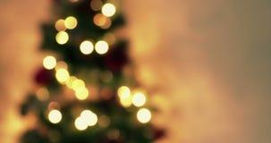 Η χρυσή περίληψη που αναβοσβήνει το θολωμένο χριστουγεννιάτικο δέντρο ανάβει bokeh στο χρυσό θερμό υπόβαθρο, εορταστικές διακοπές απόθεμα βίντεο