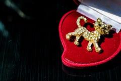 Η χρυσή πόρπη μετάλλων υπό μορφή γατακιού ή μια τίγρη cub με τις άσπρες πέτρες, rhinestones Σε ένα μαύρο στιλπνό, αντανακλαστικό  στοκ εικόνα με δικαίωμα ελεύθερης χρήσης
