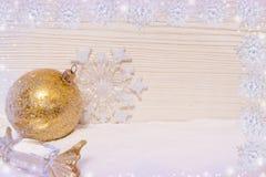 Η χρυσή σφαίρα, η καραμέλα και snowflake διακοσμήσεων Χριστουγέννων βρίσκονται στο χιόνι στο ξύλινο υπόβαθρο με snowflakes Στοκ Εικόνα