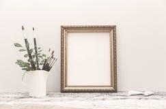 Η χρυσή χλεύη πλαισίων επάνω στις άσπρες βούρτσες πινάκων και τέχνης στοκ εικόνες με δικαίωμα ελεύθερης χρήσης