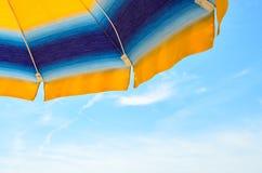Η χρωματισμένη ομπρέλα θαλάσσης, μπλε ουρανός, υπαίθριος, κλείνει κατά το ήμισυ επάνω Στοκ Εικόνα