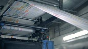 Η χρωματισμένη σελίδα εγγράφου κινείται μέσω του τυπογραφικού Τύπου Εφημερίδες εκτύπωσης στην τυπογραφία απόθεμα βίντεο