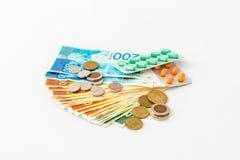Η χρωματισμένη στενόμακρη μορφή χαπιών σε μια συσκευασία βρίσκεται σε έναν σωρό των τραπεζογραμματίων και των νομισμάτων των νέων Στοκ Φωτογραφία