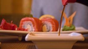 Η χύνοντας σάλτσα σόγιας για τα φρέσκα ιαπωνικά σούσια κυλά ασιατικό στενό σε επάνω εστιατορίων απόθεμα βίντεο