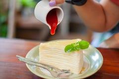 Η χύνοντας σάλτσα φραουλών χεριών επάνω crepe το κέικ στοκ εικόνες