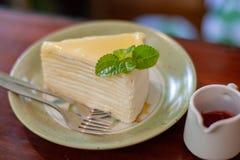 Η χύνοντας σάλτσα φραουλών χεριών επάνω crepe το κέικ στοκ εικόνα με δικαίωμα ελεύθερης χρήσης