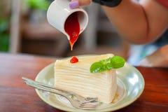 Η χύνοντας σάλτσα φραουλών χεριών επάνω crepe το κέικ στοκ φωτογραφίες