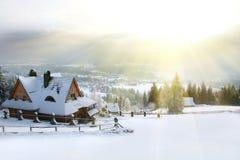 η χώρα κάλυψε τον υψηλό σπιτιών πρωινού βουνών χειμώνα χιονιού οδικών στεγών μικρό Στοκ Φωτογραφία