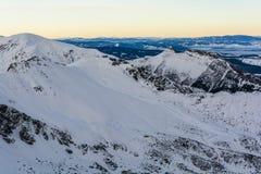 η χώρα κάλυψε τον υψηλό σπιτιών πρωινού βουνών χειμώνα χιονιού οδικών στεγών μικρό Στοκ Εικόνες