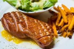 Η ψημένη στη σχάρα καπνισμένη πάπια με την κίτρινη σάλτσα μάγκο τρώει την πράσινη σαλάτα και τη γλυκιά πατάτα που τηγανίζονται με Στοκ Εικόνες