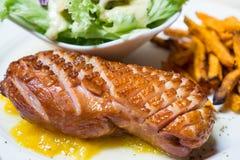 Η ψημένη στη σχάρα καπνισμένη πάπια με την κίτρινη σάλτσα μάγκο τρώει με τα τηγανητά πράσινης σαλάτας και γλυκών πατατών Στοκ Φωτογραφίες