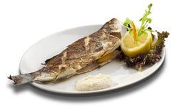 Ψημένη στη σχάρα πέστροφα στο άσπρο πιάτο που διακοσμείται με τα λεμόνια Στοκ φωτογραφίες με δικαίωμα ελεύθερης χρήσης