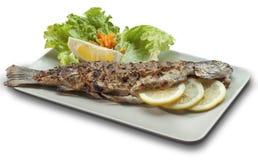 Ψημένη στη σχάρα πέστροφα στο άσπρο πιάτο που διακοσμείται με τα λεμόνια Στοκ Εικόνες